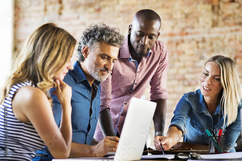 Business people working in office of a start-up company, having a meeting