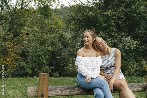 Two happy young women sitting on fence in a park