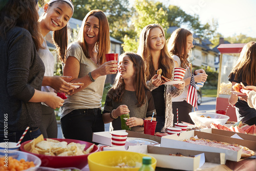 Fotografía  Girls stand talking at a block party food table, close up