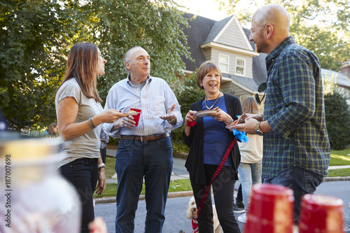 Photo  Middle aged and senior neighbours talking at a block party