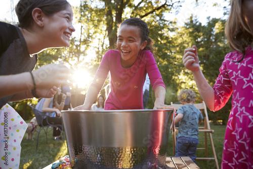 Fotomural  Three young girls have fun apple bobbing at a backyard party
