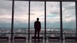 Rear view of businessman in an office with panoramic city view. Businessman