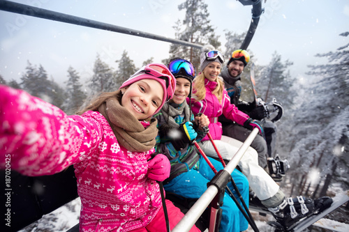 Happy family in cable car climb to ski terrain
