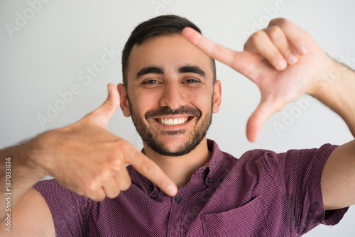 Foto  Happy Young Attractive Man Making Frame Gesture