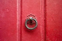 Front View Of A Round And Twisted Cast Iron Door Knocker Fitted On An Old Wooden Door Painted In Red.