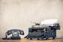 Retro Old Black Telephone And Aged Typewriter With Paper Blank On Wooden Desk Front Concrete Wall Background. Vintage Style Filtered Photo