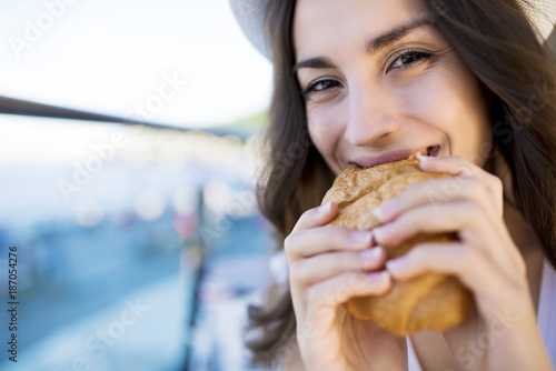 Carta da parati Attractive modern young smiling brunette woman in white hat eating fresh croissa