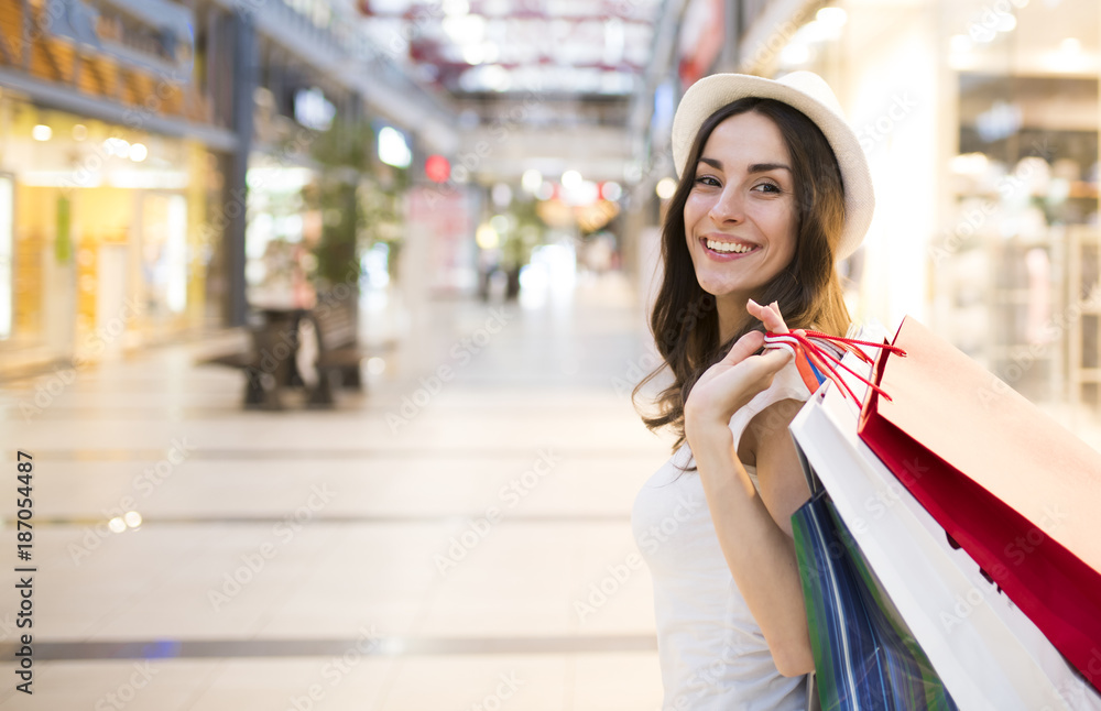 Fototapety, obrazy: Beautiful and smiling young woman doing shopping in the mall.