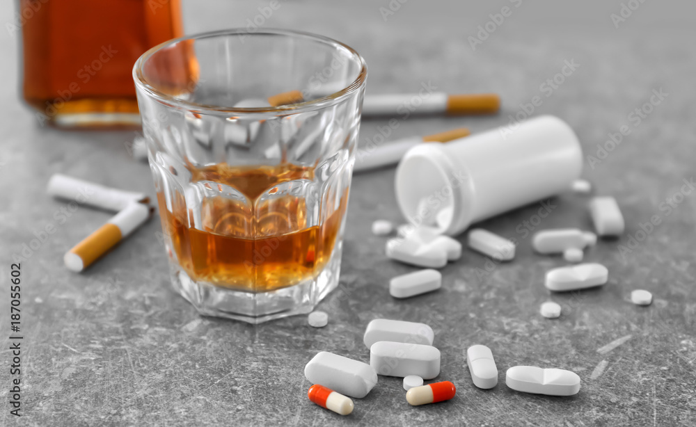 Fototapeta Glass of alcohol, cigarettes and drugs on table. Concept of bad habits