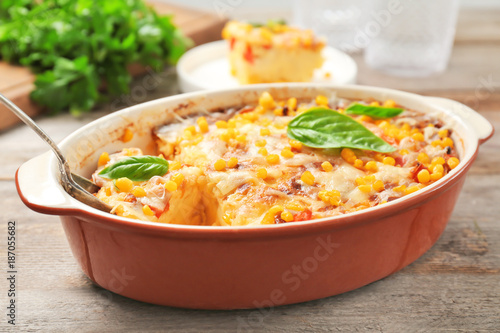 Baking dish with corn pudding on wooden table, closeup