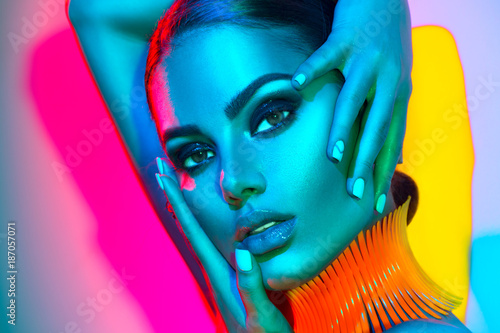 Fashion model woman in colorful bright lights with trendy makeup and manicure posing in studio