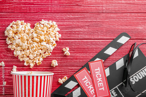 Fotografie, Obraz  Tasty popcorn, tickets and clapboard on red wooden background, top view