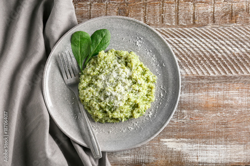 Plate with tasty spinach risotto on table, top view