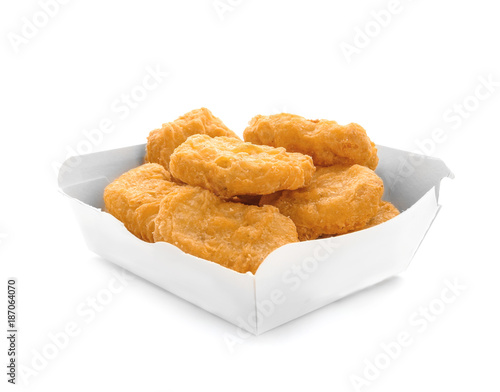 Box with tasty chicken nuggets on white background
