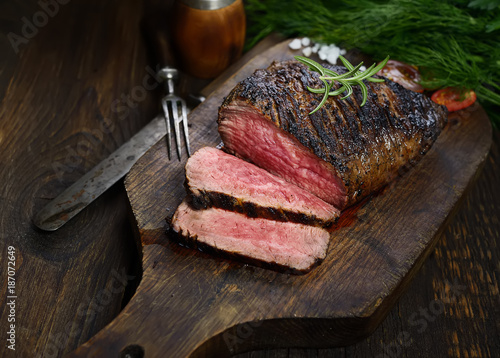 Recess Fitting Steakhouse grilled steak with rosemary on a cutting board on a black background