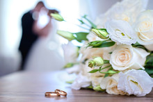 Wedding Rings And Bouquet On A Background Of Blurred Newlyweds