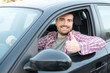Portrait of young male driver at the wheel in his vehicle