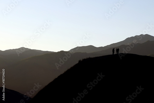 Slika na platnu silhouette of people standing on the hillside