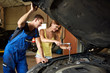 Young woman helps an auto mechanic repair a car in a garage. The girl unscrews the front right-hand stand. The guy holds the hood cover by hand