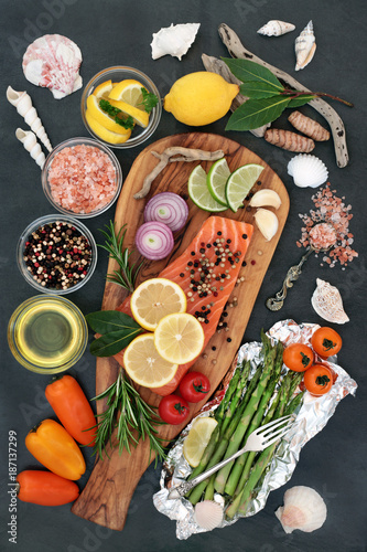 Health food for a healthy heart with fresh salmon fish, seasoning, vegetables, fruit and olive oil on an olive  wood board on slate background. High in omega 3.