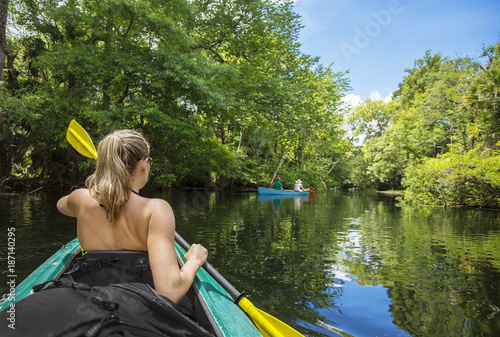 Valokuva  Woman kayaker paddling down a beautiful jungle river with two people in a canoe on a gorgeous day