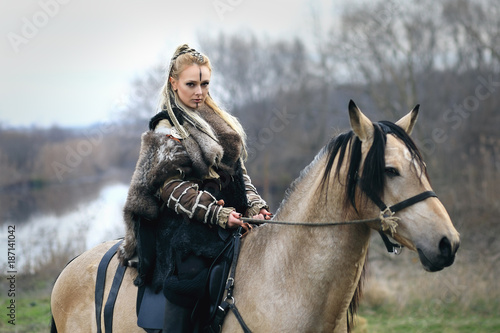 Plakát  Beautiful viking warrior woman in traditional warrior clothes riding a horse
