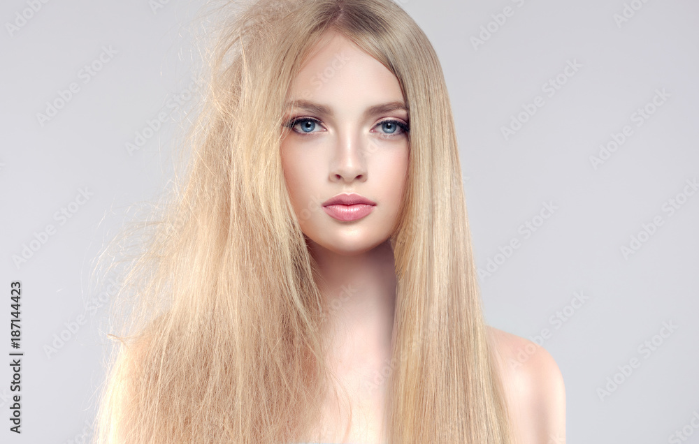 Fototapeta Hair care . Straightening ,smoothing and treatment of the hair .  Girl with straight and smooth hair on one side of the head . The second side of the head tangled and unbrushed hair .