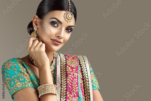Portrait of beautiful indian girl. Young hindu woman model with kundan jewelry set. Traditional India costume lehenga choli or sari