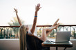 young woman with raised hands relaxing with laptop computer on a balcony on summer vocation