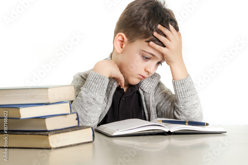 Stampa su Tela Studio portrait of young boy struggling with his homework - learning difficultie