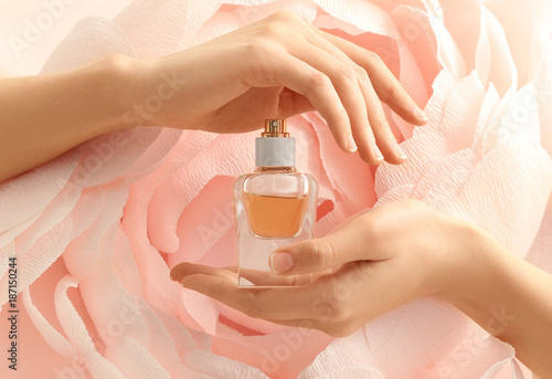 Fototapeta Hands of beautiful young woman with bottle of floral perfume against decorative artificial flower obraz