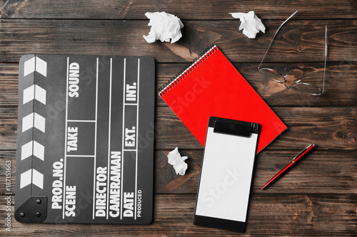Fototapeta Composition with movie clapper, clipboard and notebook on wooden background, top