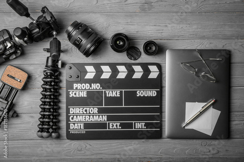 Composition with movie clapper, laptop and different lenses on grey background, top view