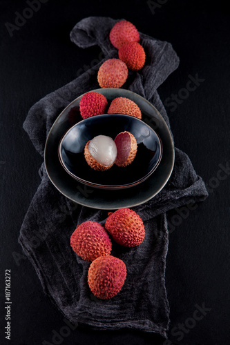 ripe, vermilion exotic lichees decorated on a slate plate kitchen table background with napkin