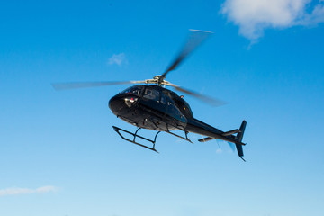 Fototapeta solo black helicopter in blue skies