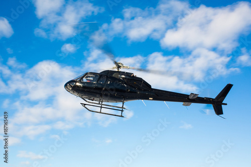 Staande foto Helicopter solo black helicopter in blue skies