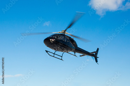 Tuinposter Helicopter solo black helicopter in blue skies