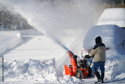 man removing snow on the driveway of the house by snow blower Canvas Print