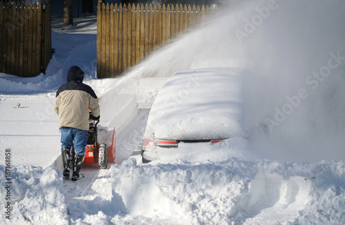 Photo man removing snow on the driveway of the house by snow blower