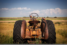 The Back End Of A Rusted Vintage Tractor Facing Out Toward Fields Under Cloudy Sky In A Rural Black And White Summer Countryside Landscape