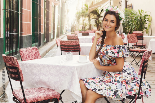 Happy woman sitting in the street cafe with a cup of hot coffee Canvas Print