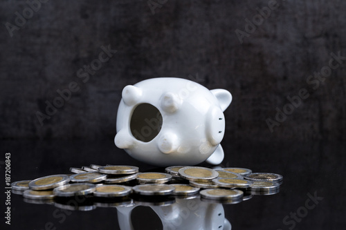 Empty piggy bank lay on dark black table with coins using as broke or personal f Poster