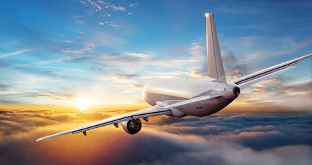 Fototapeta Commercial airplane jetliner flying above clouds in beautiful sunset light.
