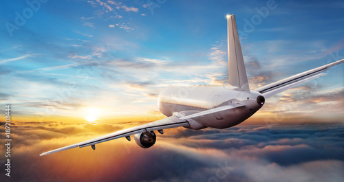 Poster Avion à Moteur Commercial airplane jetliner flying above clouds in beautiful sunset light.
