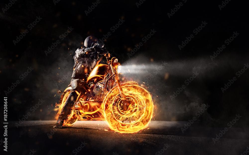 Fototapeta Dark motorbiker staying on burning motorcycle, separated on black background.