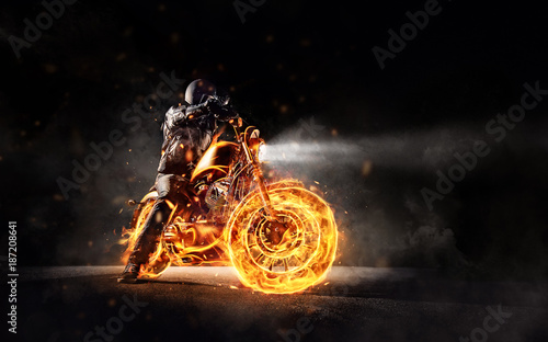 Photographie Dark motorbiker staying on burning motorcycle, separated on black background