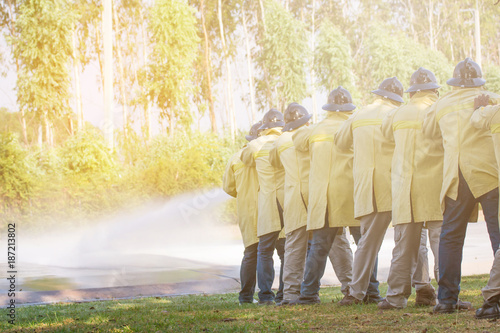 In de dag Vuur Firemen using extinguisher and water from hose for fire fighting at firefight training of insurance group. Firefighter wearing a fire suit for safety under the danger training case.