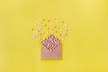 Multicolor Sweets Sugar Candy Hearts Fly Out Of Craft Paper Envelope On The Bright Yellow Background . Valentine Day. Love Concept. Gift, Message For Lover. Space For Text