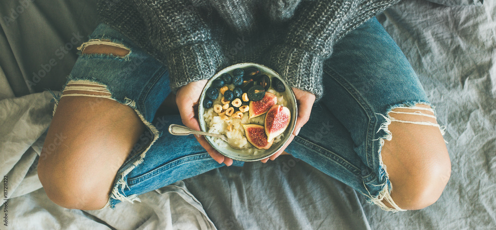 Fototapety, obrazy: Healthy winter breakfast in bed. Woman in sweater and jeans holding rice coconut porridge with figs, berries, hazelnuts, top view, wide composition. Clean eating, vegetarian, comfort food concept
