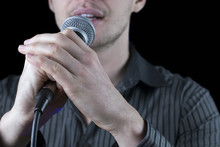 Front View Of A Man Singing To Microphone On Black Background.